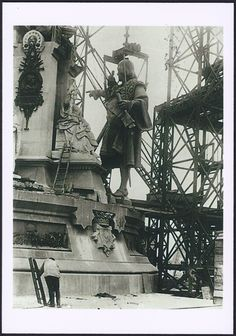 Construction of the Columbus Monument in Barcelona (1880-1888): preparing to hoist the statue of Christopher Columbus to the top of the monument. Old image on new postcard by MUHBA (Museu d'Història de Barcelona).