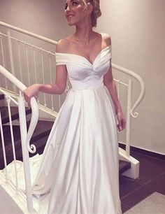 Silky white evening gown off-shoulder v-neck with high waist and train. Simple elegance.