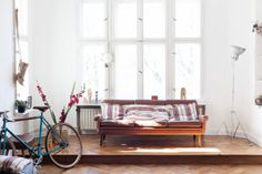 White and light brown living room interior design, simple and minimalist. I love the detail of the bike and flowers.