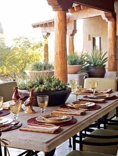 A courtyard in this Southwestern home features a long limestone dining table, the scene of many parties in this gorgeous setting - Traditional Home®  Photo: Michael Venera Design: Patty Burdick