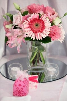 gerbera centerpiece.. maybe with the vases full of pearls or the tiny candleholders full of pearls!