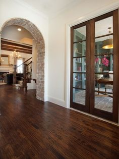 Exposed Brick Basement Arch- love the moulding on the glass doors