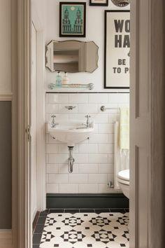 salle de bain années 50, carreaux de ciment, vasque suspendue, miroir biseauté, affiches vintage
