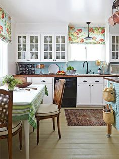 An impressive mix of repurposed flea market finds, refurbished pieces, and fresh paint update this country kitchen. A blue beaded-board backsplash installed horizontally provides a fresh twist on traditional wainscoting. Warm beige paint updates wood floors worn beyond repair. Fresh floral fabrics, wicker accents, and wall brackets beneath upper cabinetry complete the charming country design./