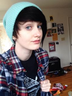[Image: A white person with black dyed hair. They are wearing a beanie and a plaid flannel shirt.]