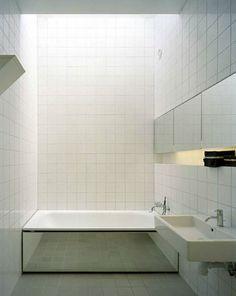 salle de bain design avec carrelage blanc sol et mur pour habiller le tablier de la baignoire un grand miroir qui rappele les portes miroirs des placards