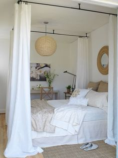 Lovely beachy bedroom with iron ceiling mounted canopy with with sheers, round woven mirror, burlap pillows, soft white bedding, jute rug an d woven pendnat chandelier.