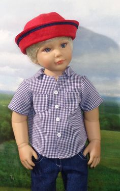 All set for school or play, Finn models navy check sport shirt, dark blue denim shorts, and a red sailor hat. The shorts are made of a dark blue denim, have white topstitching, front pockets, and elastic in casing at the waist for a smooth and easy fit. His shirt is made from a fine pima gingham check, with short sleeves, a rounded collar, and front buttons over a snap closure. The sailor style hat is made from red linen with navy middy braid trim, and is lined with a red gingham check…