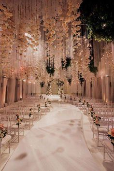 Strands of flowers and tealights hang over a curved aisle