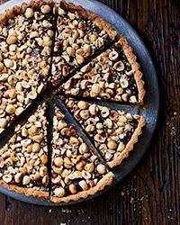 Trust me, I've made a chocolate-hazelnut tart for years and it is a crowd pleaser. Crunchy toasted nut pastry filled with dark chocolate ganache and topped with more toasted hazelnuts - perfection. I serve unsweetened softly whipped cream on the side. Hazelnut Recipes, Tart Recipes, Chocolate Recipes, Wine Recipes, Sweet Recipes, Dessert Recipes, Chocolate Ganache Filling, Chocolate Hazelnut, Chocolate Tarts