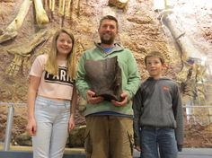 Paul Hollingshead and his family show off their fossil find (elephant scapula) behind an Iguanodont exhibit.