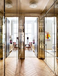 Antiqued mercury glass sheathes a hallway fitted with H. Theophile door hardware at the Manhattan home of architect Steven Harris and interior designer Lucien Rees Roberts