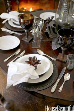 """Centerpieces don't have to be a floral arrangement. """"I select artifacts my children or I have collected. These pieces have a richness of spirit, a softness of age, and a story,"""" says home furnishings designer Jan Barboglio. Dinner plates from Pottery Barn."""