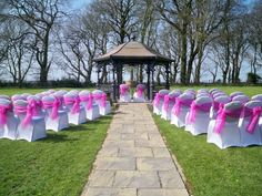 White chair covers with two tone organza hot pink sashes set for an outside wedding ceremony x