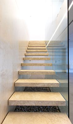 Chiralt Arquitectos I Escalera de peldaño volado de piedra natural con barandilla de cristal.