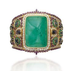 AN EMERALD, RUBY, SAPPHIRE AND DIAMOND BANGLE  Centering upon a large sugarloaf cabochon emerald, to the openwork tapering band set with sapphire, emerald, ruby and diamond foliate motifs, mounted in gold, inner diameter 7.0 cm