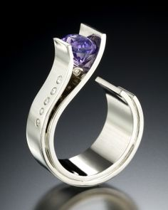 Fiore Sapphire - Gemstones bloom forth from graceful petals of gold. This ring features a distinctive purple sapphire set in 14kt white gold with .12 carats total weight of VS G diamonds. This ring is available by order featuring a variety of stones in yellow or white gold.