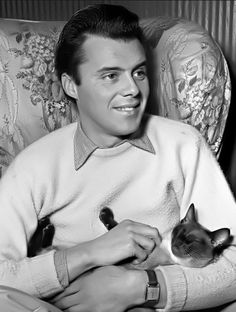 Dirk Bogarde with a cat on his lap