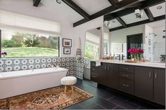 I love the mix of this large bathroom with the black tile floor, brown stained cabinets, and antique rug.  It all works together and the tiles are the perfect addition.