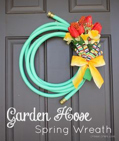 Garden Hose Spring Wreath DIY- materials: -15 foot garden hose -Twist tie -Silk flowers -Butterfly clip (optional, decor) -Garden gloves -Ribbon. Cute! Would make a great house warming gift