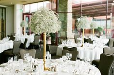 Centerpieces of slender gold vases are brimming with baby's breath. Wedding Venue: Desert Willow Golf Resort   Photographer: Katie McGihon Photography
