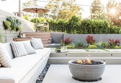 Sunken patio is filled with a concrete bench lined with white outdoor cushions and gray striped outdoor pillows faces a concrete bowl fire pit surrounded by black river rocks.
