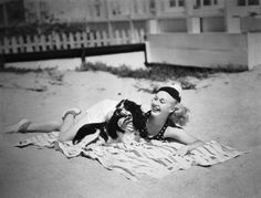 1936: American dancer and actress Ginger Rogers stretches out on a beach towel with her pet spaniel