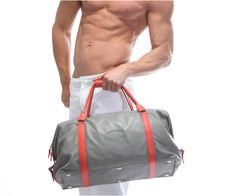 Sportsbag in grey and orange, lined with seude inside, model wearing our essential wear lounge pants in white.
