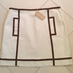 NWT Michael Kors Collection Cotton/Leather Skirt This new with tags, and unworn skirt is ecru 100% cotton with chestnut leather accents. In perfect condition. Please note this is a collection piece and not from the less expensive mmk line. Michael Kors Skirts