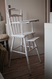a vintage baby chair painted shabby white