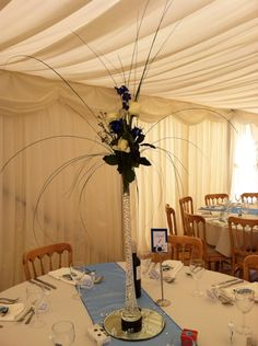 Wedding at fishlake mill using slim glass vases with roses, blue delphiniums, wax flower bear grass and steel grass.