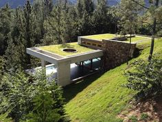 """""""From a distance, it might be hard to tell that there's a house hidden within this lush Dominican Republic landscape. But look again and you'll see how VASHO architects skillfully tucked this 5,380 square foot house into a steep hillside overlooking spectacular pine-studded views. Large green-roofed terraces create the illusion that the house is an extension of the hill's natural contours."""""""