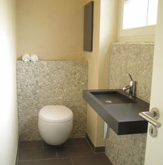 Gäste WC mal mit Kieseln an der Wand - stylish!