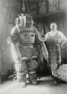 Chester E. Macduffee next to his newly patented, 250 kilo diving suit, 1911