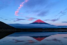 In this stunning sunset photo by Agustin Rafael Reyes, we see the sun's rays kissing the tip of Mount Fuji, turning it red as clouds below streak across.