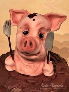 All edible pig with knife and fork sitting in mud made out with chocolate cake.