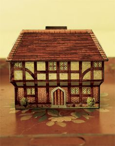 1925, the English manufacturer Huntley, Boorne & Stevens produced this lithographed Tudor-style cottage biscuit tin.