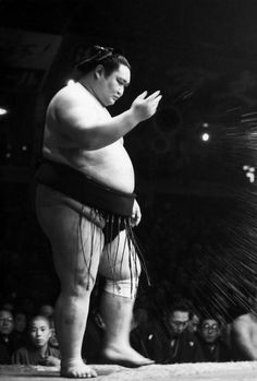 Sumo fighter scattering salt on the floor, as a purification rite before the beginning of a match, Tokyo, 1951 by Werner Bischof