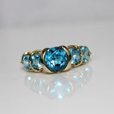 Offered today is a lovely estate ring. It is a 10k yellow gold ring with beautiful Blue Topaz gems. The Topaz stones total approximately 4 carats. The