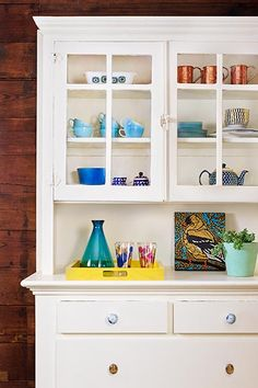 A dining room hutch, original to the house, gets added personality with unmatched ceramic and glass knobs by Anthropologie.