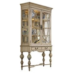 Display cabinet with three wood-framed glass shelves and turned detailing. Includes one can light and two drop-front drawers.    Product...