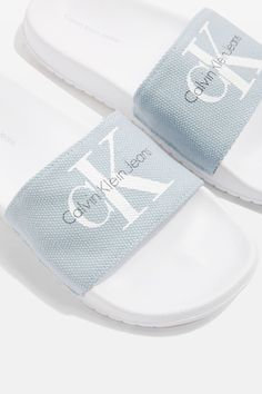 Look to an iconic brand to elevate your summer footwear with the blue Jean slider by Calvin Klein. Pair the look with frayed hem white jeans and a co-ordinating CK logo top.