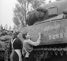 """Dutch girls write slogans and messages for friends and relatives in other towns on a tank after the liberation of Breda by the Polish 1st Armoured Division. Civilians in occupied countries would write messages on the tanks of their liberators, hoping their friends or relatives would see the messages. On the tank you can see names, addresses and """"Alles goed"""" (""""All is good"""" in Dutch). Breda, North Brabant, the Netherlands. November 1944."""