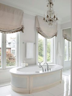 Tall, elegant proportioned windows orient the views in this grandly styled bathroom. Placement of the oversize tub in between the windows helps to conquer placement issues in the room. The subtle gray-rose and neutral color s