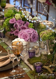 A centerpiece of branches, moss, crystals, calla lilies and purple roses tops a long wooden table. #weddingcenterpiece
