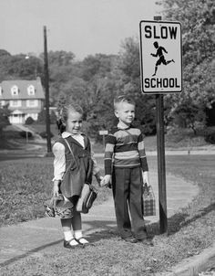 Brother and sister waiting for the school bus, 1957, lunch boxes in hand.