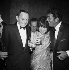 Sinatra, MacLaine, Martin 	  1965: EXCLUSIVE Left to right, American singer and actor Frank Sinatra, wearing a tuxedo, American actor Shirley MacLaine, wearing a sari, and American singer and actor Dean Martin (1917 - 1995), wearing a tuxedo, laughing at one of Martin's opening nights, Hollywood, California. Martin is holding a cigarette and MacLaine and Sinatra are holding drinks.
