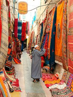 a street open market in essaouira,morocco with colourful carpets and a sale person Places Around The World, The Places Youll Go, Places To Go, Around The Worlds, Design Marocain, Style Marocain, Paises Da Africa, North Africa, Morocco Travel
