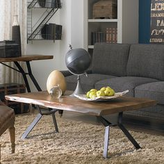 With a classic charm and air of sophistication, this hand-crafted coffee table cut from from a thick Acacia slab sits atop a sleek, hand-forged iron base to create a fusion of natural and industrial e