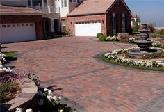 Interlocking pavers can be used to create sophisticated driveway designs. This one has a traditional style with contrasting edging and decorative bands. By Genesis Stoneworks in Southern California. Learn the pros and cons of interlocking paver driveways at http://www.landscapingnetwork.com/driveways/pavers.html